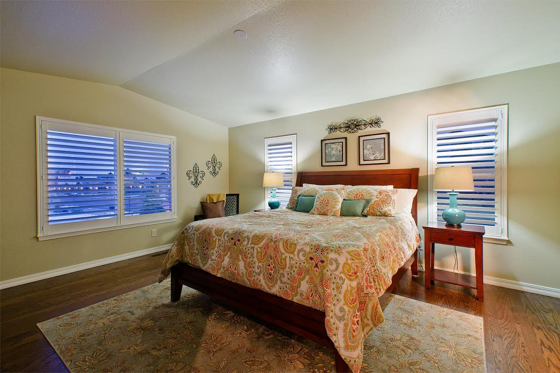 Master Bedroom with Plantation Shutters and Wood Floors